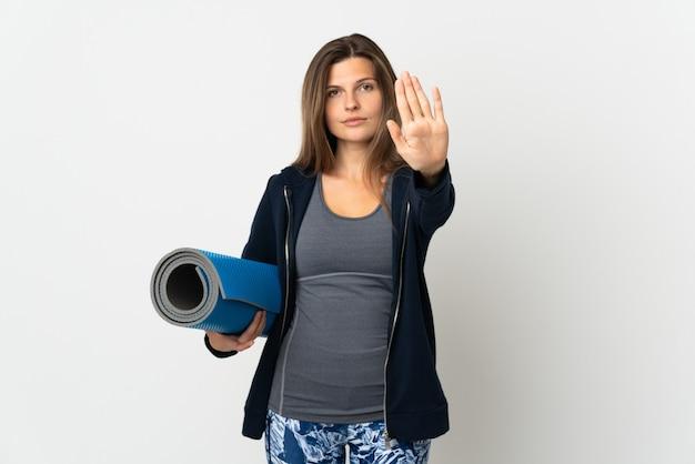 Словацкая девушка идет на занятия йогой, изолированные на белой стене, делая жест стоп