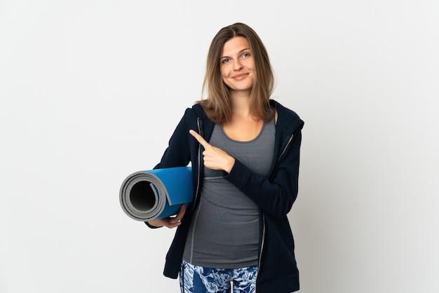 Словацкая девушка идет на занятия йогой, изолированные на белой стене, указывая в сторону, чтобы представить продукт