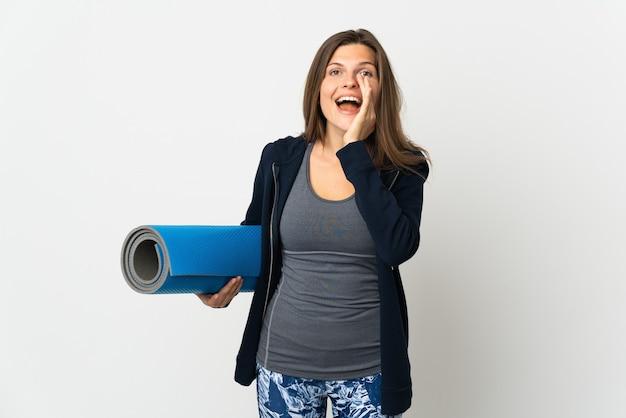 Словацкая девушка идет на занятия йогой, изолированные на белой стене, кричит с широко открытым ртом