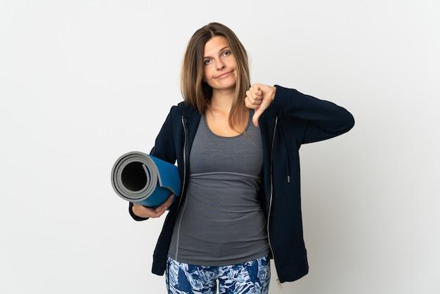 Словацкая девушка идет на занятия йогой, изолированные на белой стене, показывая большой палец вниз с негативным выражением лица