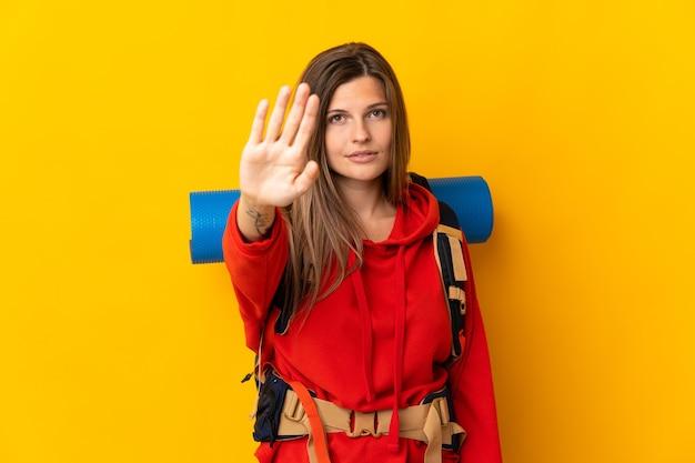 중지 제스처를 만드는 노란색 배경에 고립 된 큰 배낭 슬로바키아어 산악인 여자