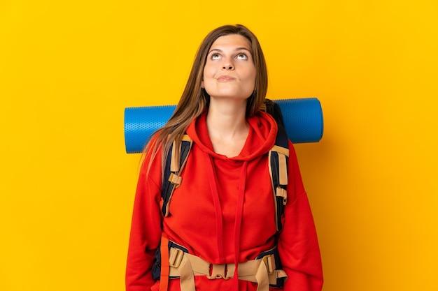 Словацкая альпинистка с большим рюкзаком изолирована на желтой стене и смотрит вверх