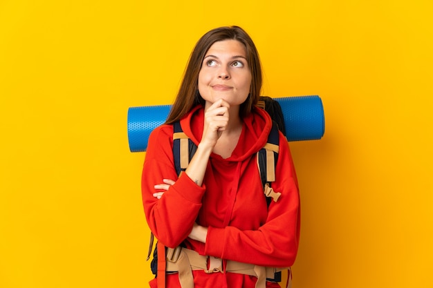 疑いと思考を持っている黄色の壁に分離された大きなバックパックを持つスロバキアの登山家の女性