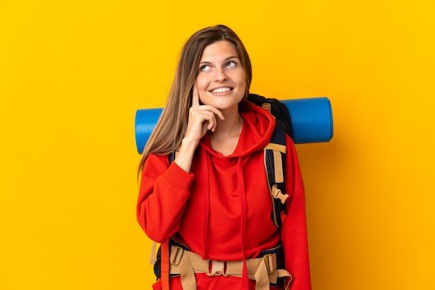 見上げながらアイデアを考えて黄色の壁に分離された大きなバックパックを持つスロバキアの登山家の女性