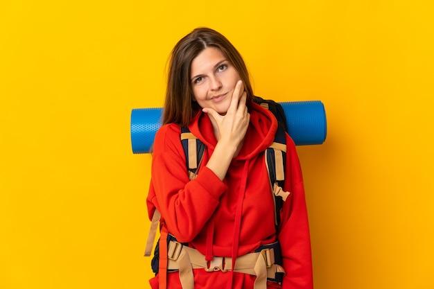 黄色の壁思考で隔離の大きなバックパックを持つスロバキアの登山家の女性