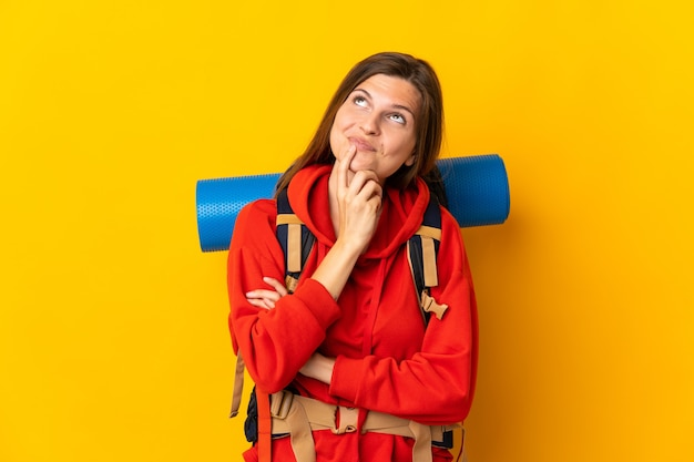 Slovak mountaineer woman with a big backpack isolated on yellow background having doubts while looking up