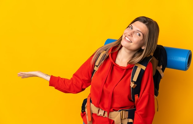 Slovak mountaineer woman with a big backpack isolated on yellow wall extending hands to the side for inviting to come