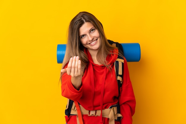 Slovak mountaineer woman with a big backpack isolated on yellow wall inviting to come with hand. happy that you came