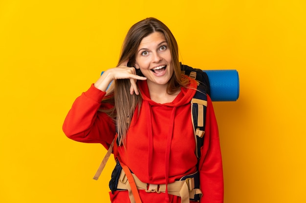 Slovak mountaineer woman with a big backpack isolated on yellow wall making phone gesture. call me back sign