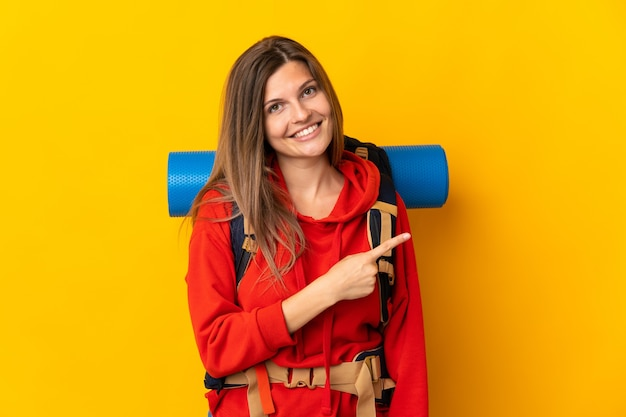 Slovak mountaineer woman with a big backpack isolated on yellow wall pointing to the side to present a product
