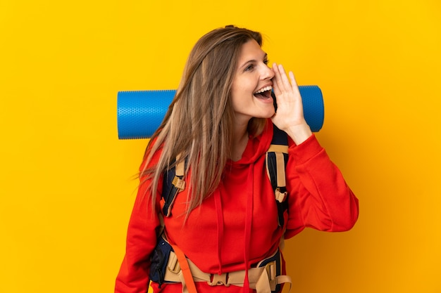 Slovak mountaineer woman with a big backpack isolated on yellow wall shouting with mouth wide open to the side