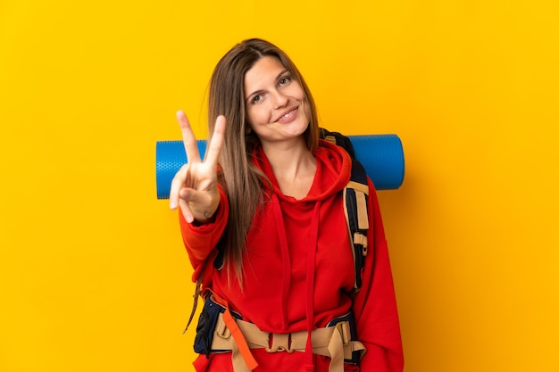 Slovak mountaineer woman with a big backpack isolated on yellow wall smiling and showing victory sign