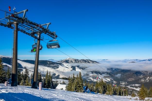 Slovak ski resort jasna. blue sky and light fog between the mountain peaks. snow glistens in the sun. chair ski lift