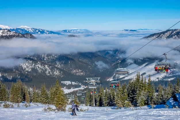Slovak ski resort jasna. snow glistens in the sun. blue sky and light fog between the mountain peaks. chair ski lift and skiers