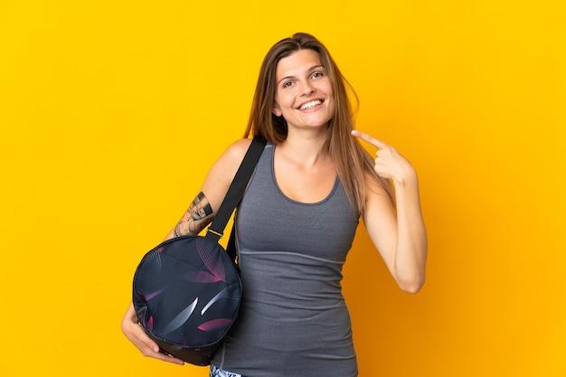 노란색 배경에 격리된 스포츠 가방을 들고 엄지손가락을 치켜드는 슬로바키아어 스포츠 여성
