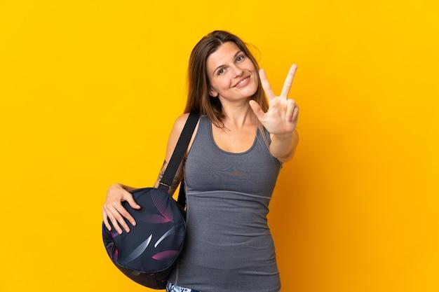 幸せな黄色の背景に分離されたスポーツバッグと指で3を数えるスロバキアスポーツ女性