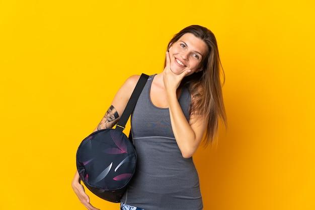 Словацкая спортивная женщина с спортивной сумкой, изолированной на желтом фоне, счастлива и улыбается