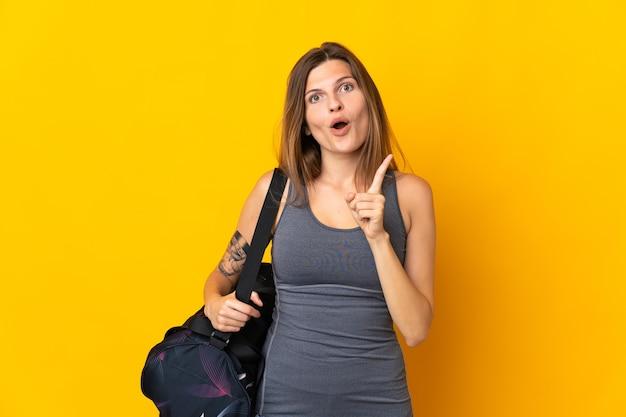 손가락을 들어 올리는 동안 솔루션을 실현하려고 노란색 배경에 고립 된 스포츠 가방 슬로바키아어 스포츠 여자