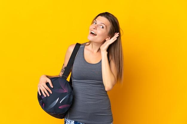귀에 손을 넣어 뭔가를 듣고 노란색 배경에 고립 된 스포츠 가방 슬로바키아어 스포츠 여자