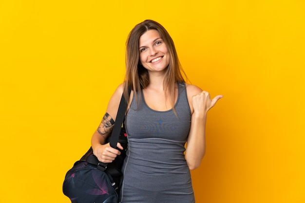 제품을 제시하기 위해 측면을 가리키는 노란색 배경에 고립 된 스포츠 가방 슬로바키아어 스포츠 여자