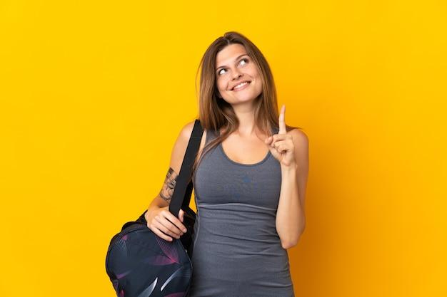 좋은 아이디어를 가리키는 노란색 배경에 고립 된 스포츠 가방 슬로바키아어 스포츠 여자