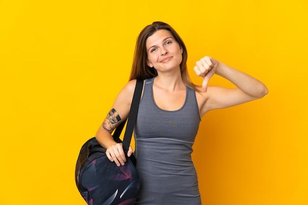 否定的な表現で親指を示す黄色の背景に分離されたスポーツバッグを持つスロバキアスポーツ女性
