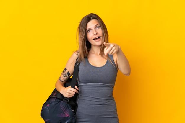 노란색 배경 놀라게 하 고 앞을 가리키는에 고립 된 스포츠 가방 슬로바키아어 스포츠 여자