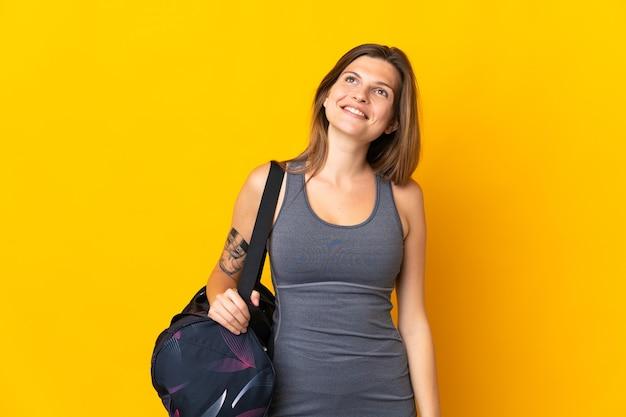 찾고있는 동안 아이디어를 생각하는 노란색 배경에 고립 된 스포츠 가방 슬로바키아어 스포츠 여자