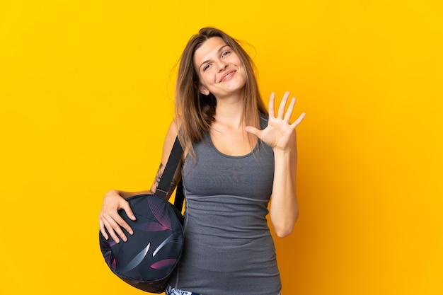 Словацкая спортивная женщина со спортивной сумкой изолирована на желтой стене, считая пять пальцами