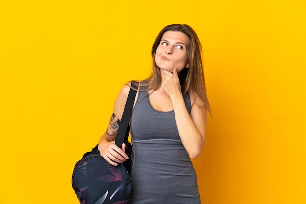 疑いと思考を持っている黄色の壁に分離されたスポーツバッグを持つスロバキアのスポーツ女性