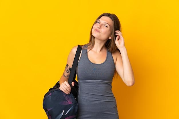 疑いを持って黄色の壁に分離されたスポーツバッグを持つスロバキアのスポーツ女性