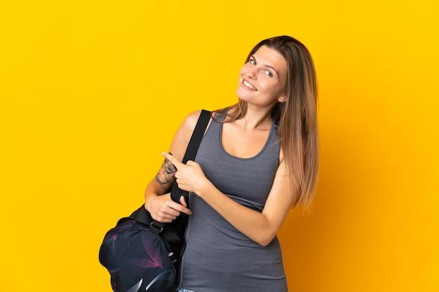다시 가리키는 노란색 벽에 고립 된 스포츠 가방 슬로바키아어 스포츠 여자