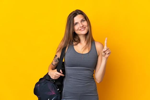 Словацкая спортивная женщина со спортивной сумкой, изолированной на желтой стене, показывает и поднимает палец в знак лучших