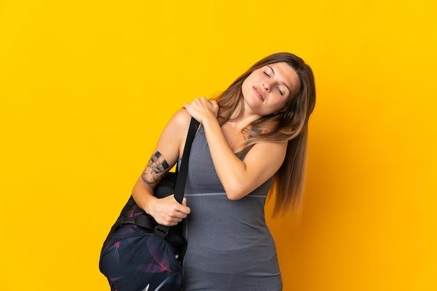 努力したために肩の痛みに苦しんでいる黄色の壁に隔離されたスポーツバッグを持つスロバキアのスポーツ女性