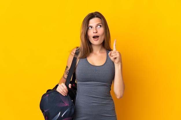 손가락을 가리키는 아이디어를 생각하는 노란색 벽에 고립 된 스포츠 가방 슬로바키아어 스포츠 여자