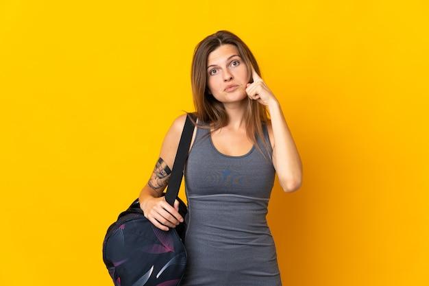 アイデアを考えて黄色の壁に分離されたスポーツバッグを持つスロバキアのスポーツ女性