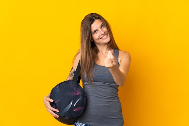 Slovak sport woman with sport bag isolated on yellow wall making money gesture