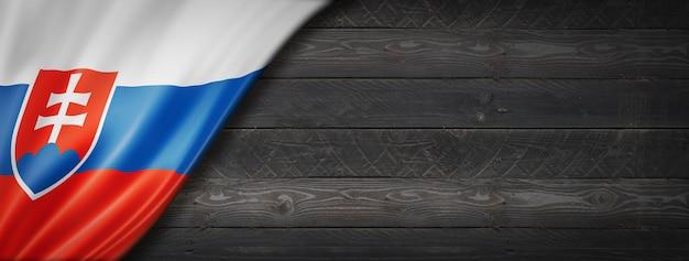 黒い木の壁にスロバキアの旗。水平方向のパノラマバナー。