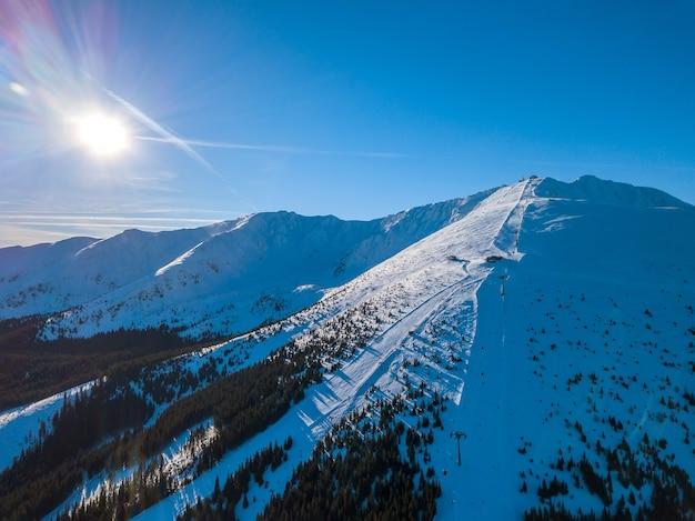 Словакия. горнолыжный курорт ясна в солнечную зимнюю погоду. горнолыжные склоны в лесистых горах. солнце ярко светит в голубом небе. с высоты птичьего полета