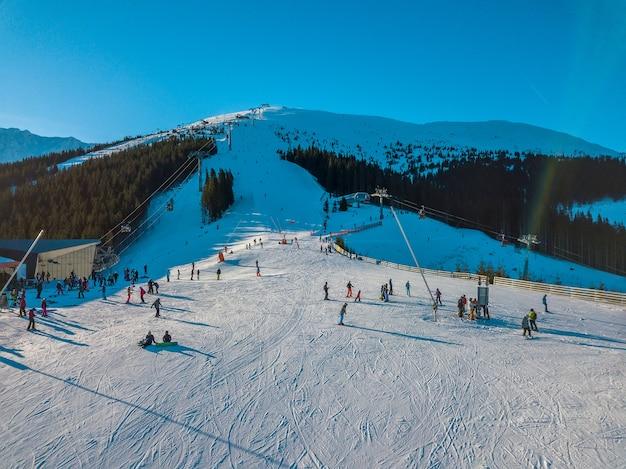 スロバキア。晴れた日の冬のジャスナ。樹木が茂った山々のスキー場。青い空と太陽が明るく輝いています。航空写真