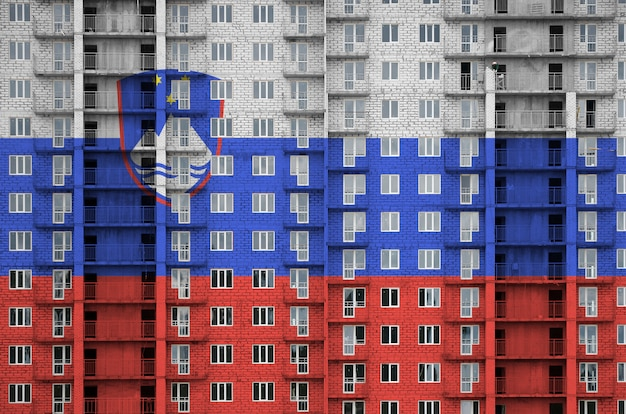 Slovenia flag depicted in paint colors on multi-storey residencial building under construction.
