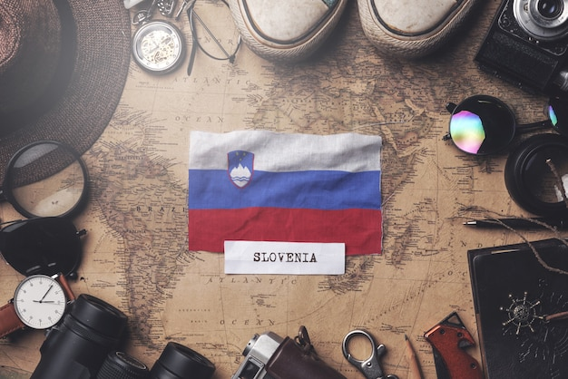 Slovenia flag between traveler's accessories on old vintage map. overhead shot