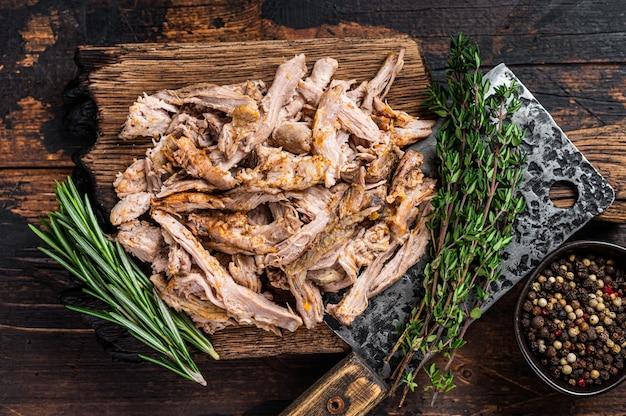 정육점 식칼이 있는 나무 판자에 천천히 요리된 puilled 돼지고기. 어두운 나무 배경입니다. 평면도.