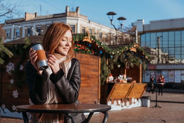 都市環境でのスローライフ、アーバンスローライフ、マインドフルネス、瞬間を楽しむ、ワークライフバランス。太陽を楽しんで飲んでいる若い赤毛の女性は、冬の街の通りでコーヒーをテイクアウトします。