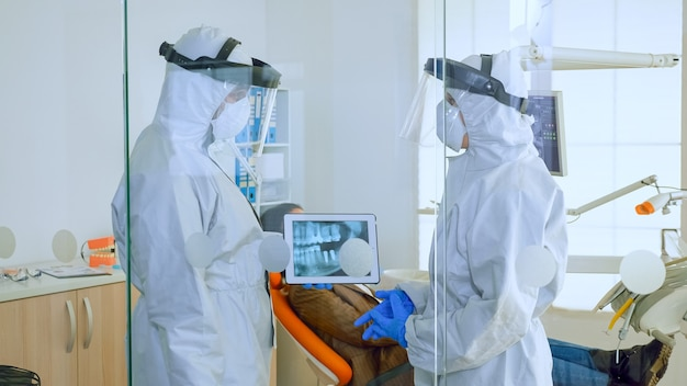 歯科室でタブレットを使用して歯のx線を分析し、患者が口腔病学の椅子を待っている間に世界的大流行の手術を計画しているppeスーツを持った口腔病学の医師のスローモーションクローズアップ