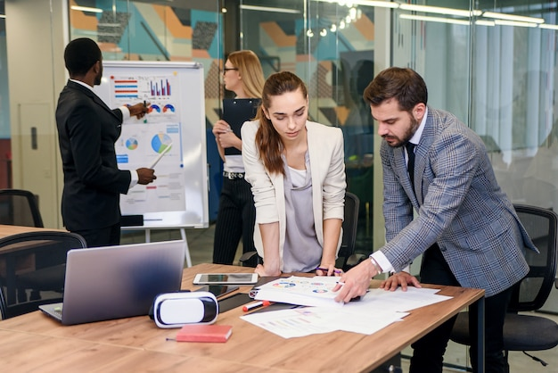 Slow motion of handsome enterprising bearded businessman standing near boardroom table with his attentive female colleague and explaining the reports data