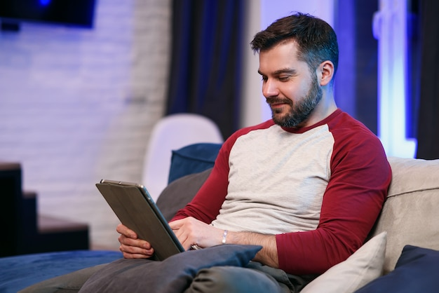 Slow motion of likable modern good-natured 30-aged man with well-groomed beard which resting on the sofa at home and browsing apps on tablet pc with lucky smile
