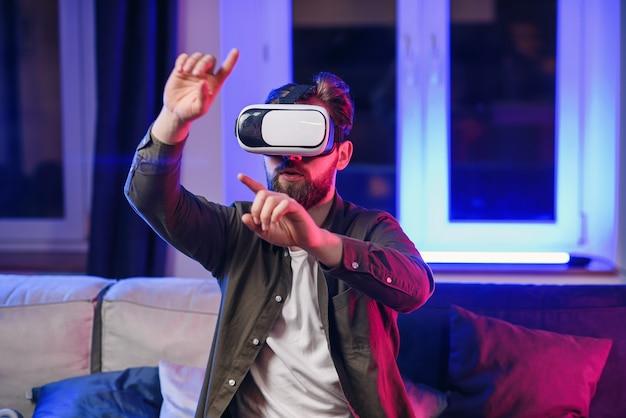 拡張現実ゴーグルで架空のタッチスクリーンに取り組んでいる、ひげのある好感の持てる陽気な陽気な男のスローモーション