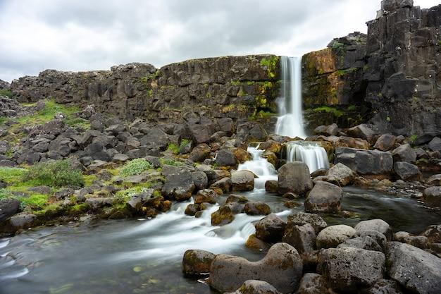 Медленное движение водопада оксарарфосс в национальном парке тингвеллир, исландия.