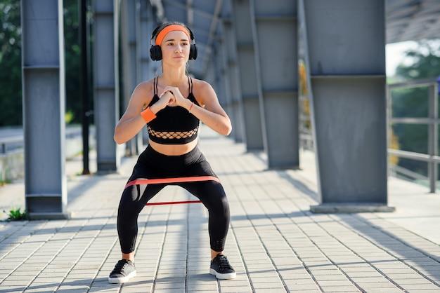 特別なスポーツグラウンドでの彼女のスポーツトレーニング中にファブリック戦利品バンドでスクワット運動をしているイヤホンで抵抗バンドフィットネスガールのスローモーション